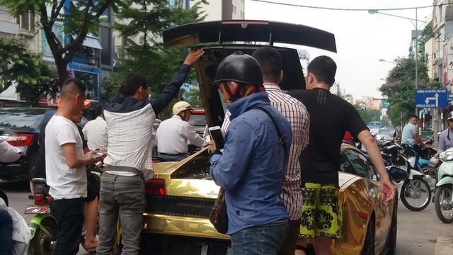 Nhiều người dân hỗ trợ người cầm lái siêu xe này dập tắt đám khói ở khoang động cơ