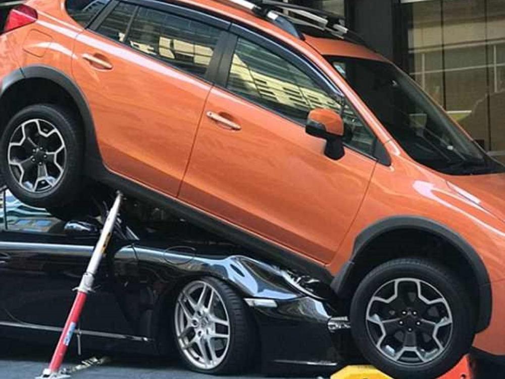 Subaru XV màu cam tươiđè đầu cưỡi cổ chiếc xe thể thao mui trần màuđen