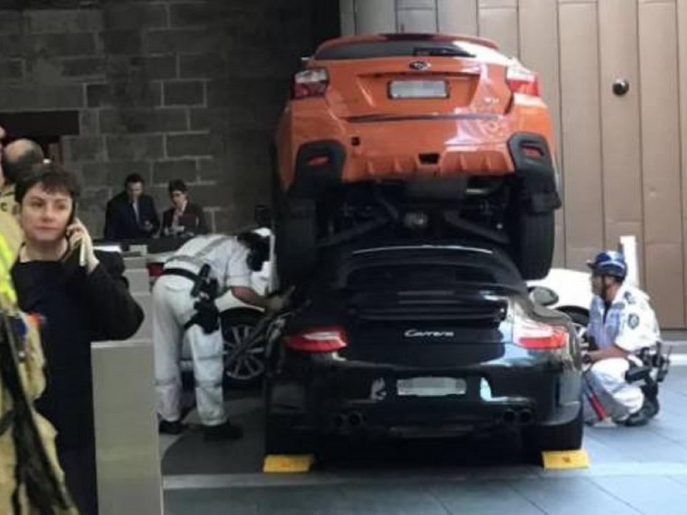 Lực lượng chức năngđang cắt phần mui mềm của Porsche 911 Carrera S màuđenđể lôi người cầm lái ra bên ngoài