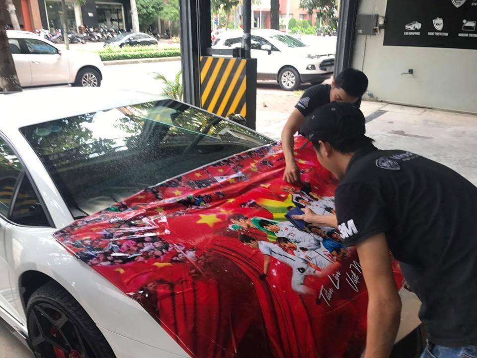 Hình ảnh thầy trò Park Hang-seo xuất hiện trên nắp capô siêu xe Lamborghini Aventador LP700-4 màu trắng để cổ vũ cho tinh thần Olympic Việt Nam