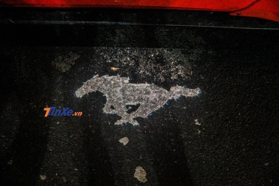 Logo ngựa hoang hiện dưới nền gạch khi mở cửa xe Ford Mustang
