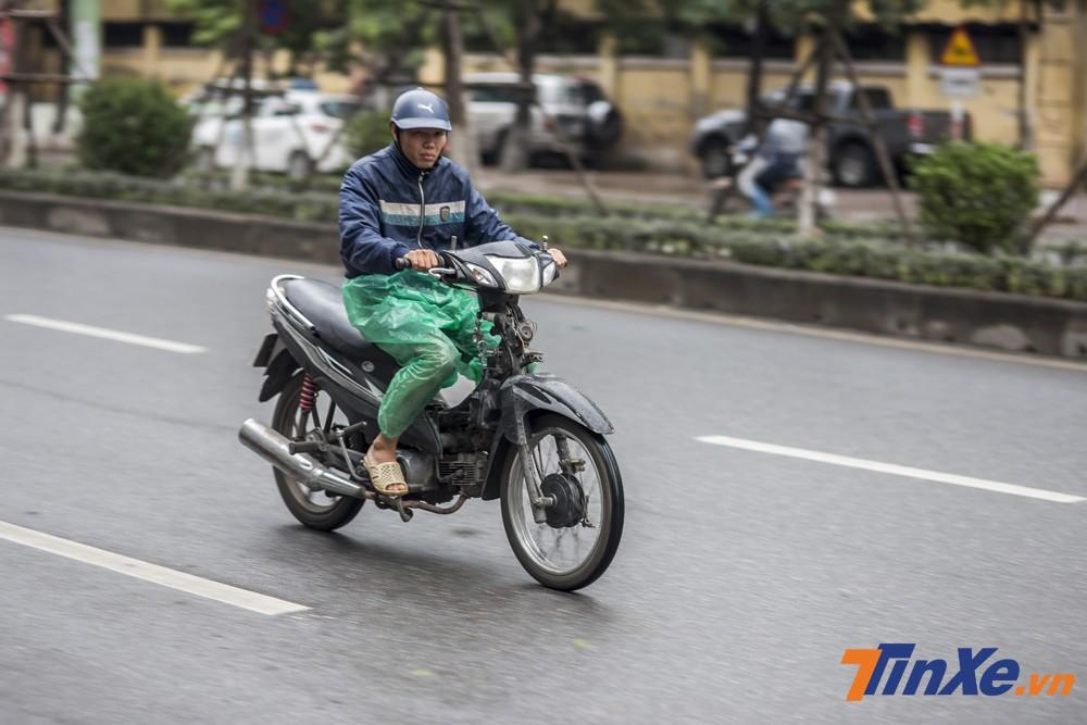 Trong gió rét và mưa của đợt lạnh này, không chỉ quần áo rét mà ngay cả áo mưa cũng được tận dụng để giữ ấm cho những người đi xe máy.