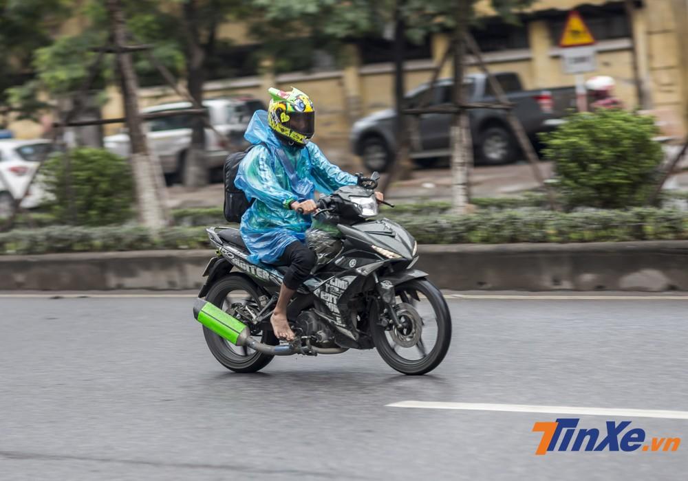 Một biker cùng chiếc mũ AGV Turtle cũng phải mặc áo mưa giấy để chống chọi với mưa và rét.