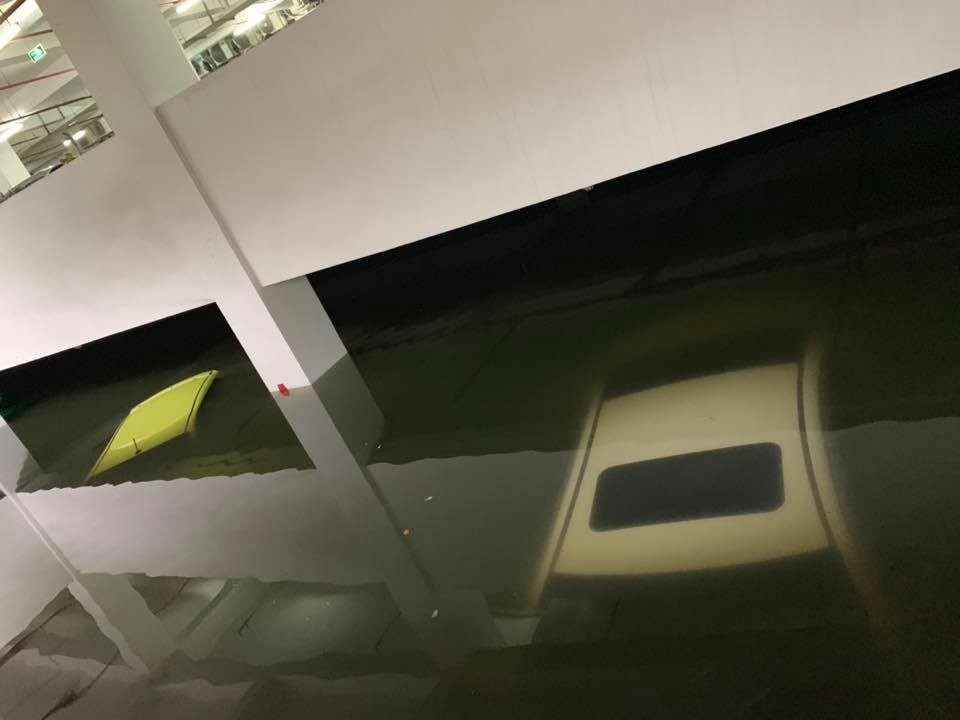 Những chiếc ô tô nằm trong hầm đỗ xe của tòa nhà kể trên bị chìm trong nước