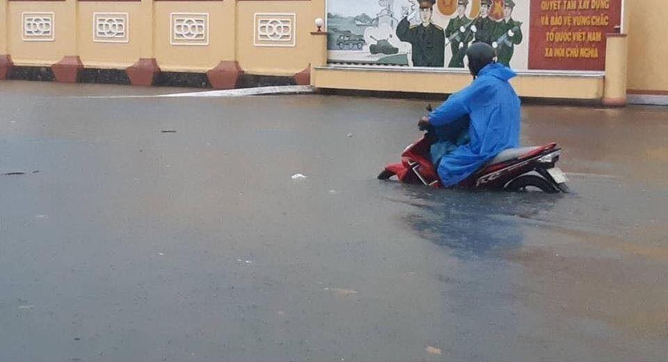 Dù đường ngập nặng nhưng một người đi xe máy vẫn cố gắng giữ ga vượt qua