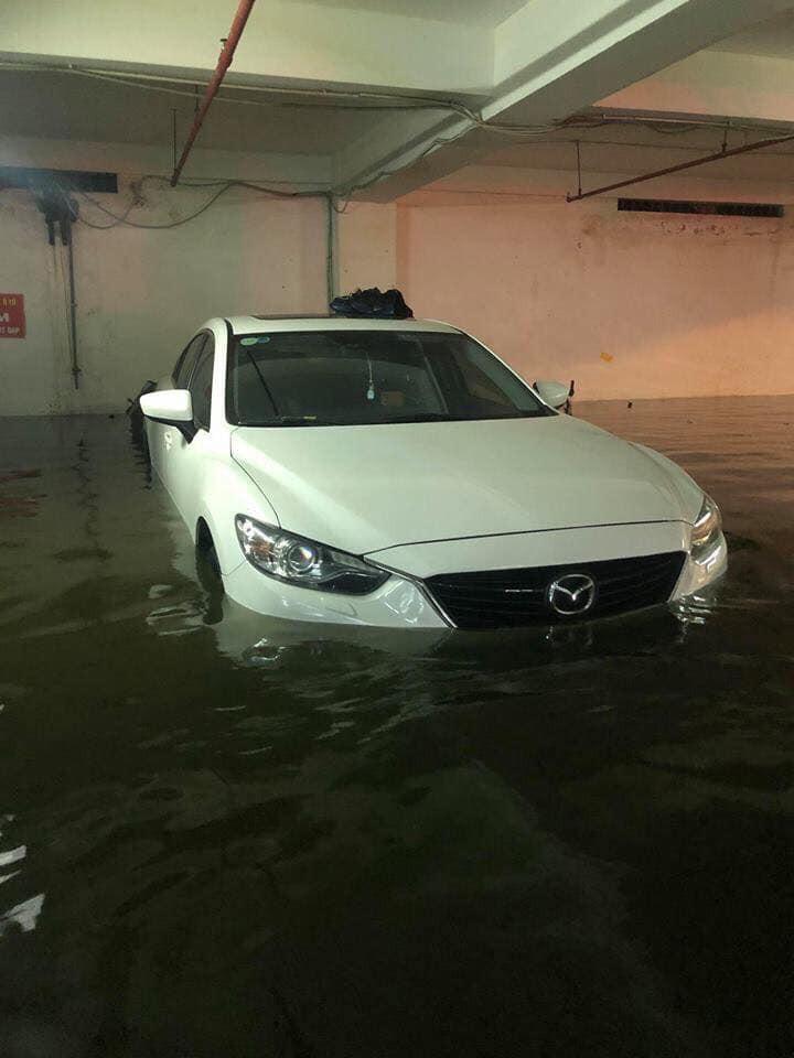 Một chiếc ô tô Mazda nằm ngâm trong nước ngập ở hầm đỗ xe