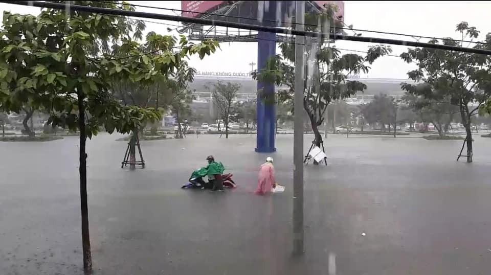 Những người đi xe máy vật vã trên đường ngập nước