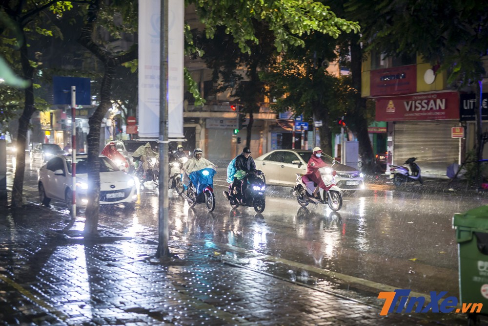 Nhiều người âm thầm lái xe dưới trời mưa và rất ít các cổ động viên với cờ, trống,...