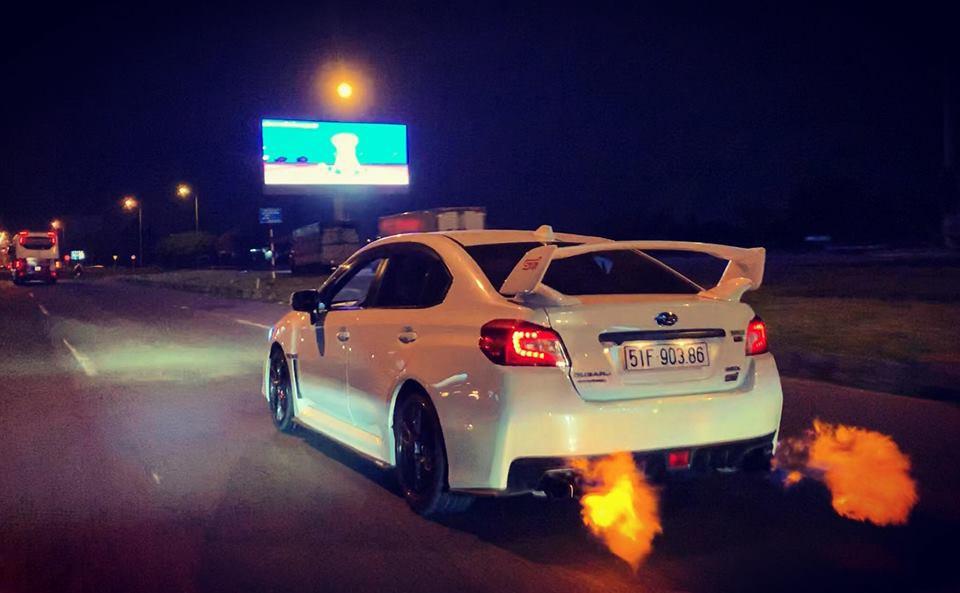 Những ngọn lửa phụt ra từ ống xả của chiếc Subaru WRX STI màu trắng khi di chuyển trên đường phố