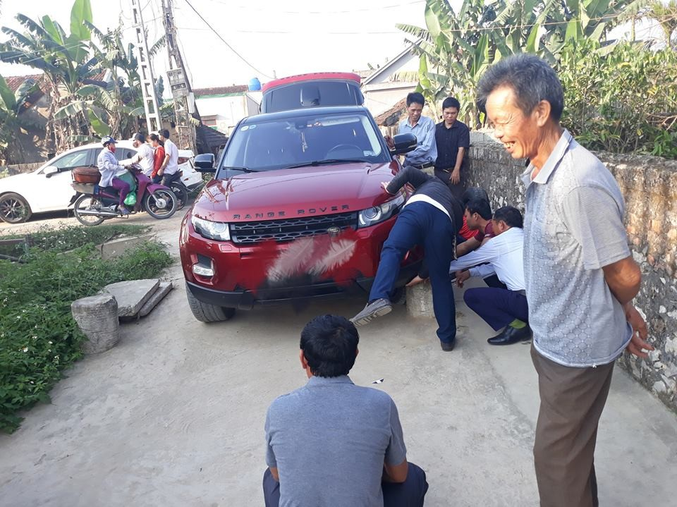 Dân làng nhanh chóng hỗ trợ chủ nhân chiếc Range Rover Evoque màu đỏ không may gặp nạn