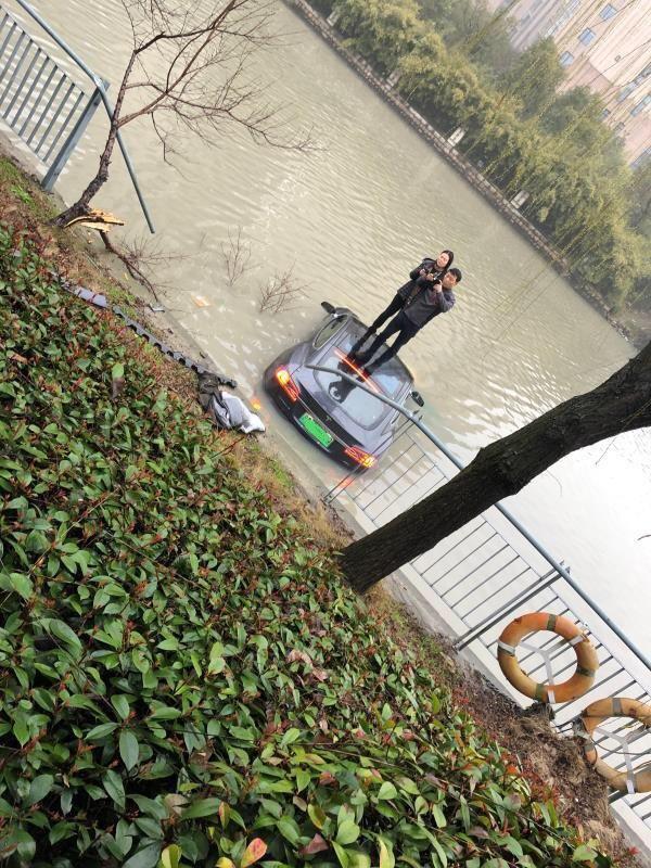 Vợ chồng anh Xiao Chen đứng trên nóc của chiếc Tesla Model S bị ngập dưới sông