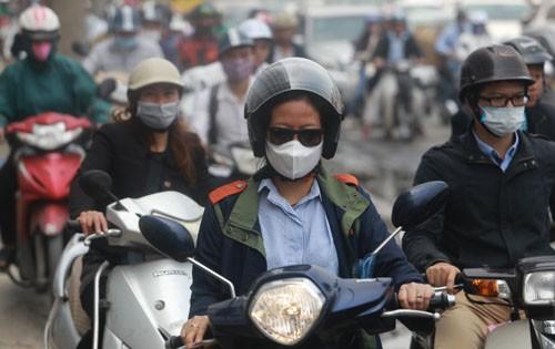 Người đi xe máy đeo khẩu trang tránh bụi trên đường Minh Khai