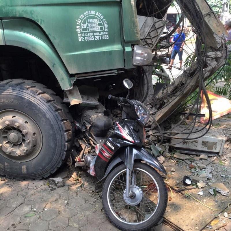 Chiếc xe máy của người phụ nữ bị kẹt dưới gầm xe ben