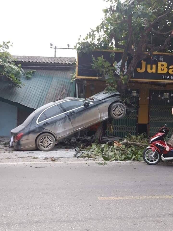 Chiếc xe sang Mercedes-Benz C-Class gác đầu lên thân cây bàng trên vỉa hè