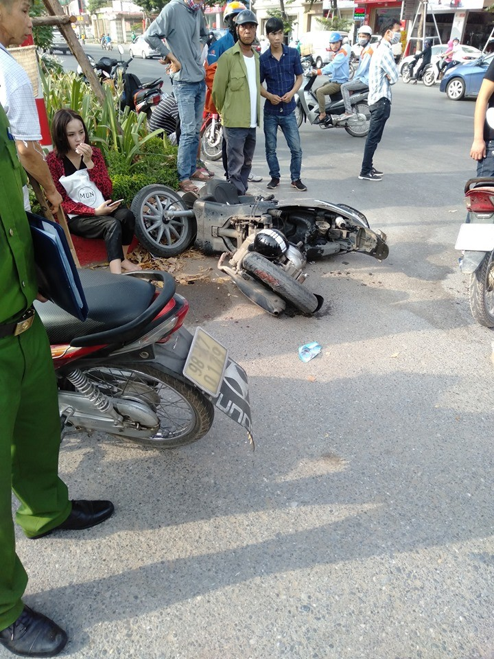 Cô gái bị thương ngồi thẫn thờ bên chiếc xe tay ga gãy làm đôi