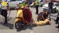 Váy bị cuốn vào bánh xe máy điện, cô gái nằm khóc giữa đường
