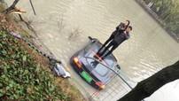 Tesla Model S lao xuống sông, cặp đôi leo ra ngoài và đứng trên nóc xe để chụp ảnh