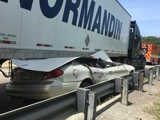 Ô tô con bị hất văng lên không trung rồi trượt vào gầm xe container, tài xế thoát chết khó tin