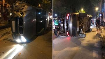 Hà Nội: SUV hạng sang BMW X5 đâm gốc cây, lật ngang và đè vào xe máy