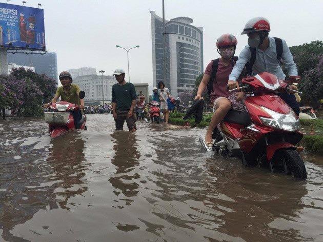 Người dân dùng xe máy để lội nước trên đường ngập