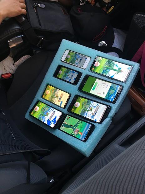 Hình ảnh tài xế ngồi sau vô lăng cùng 8 chiếc điện thoại chơi Pokémon GO ở bên cạnh