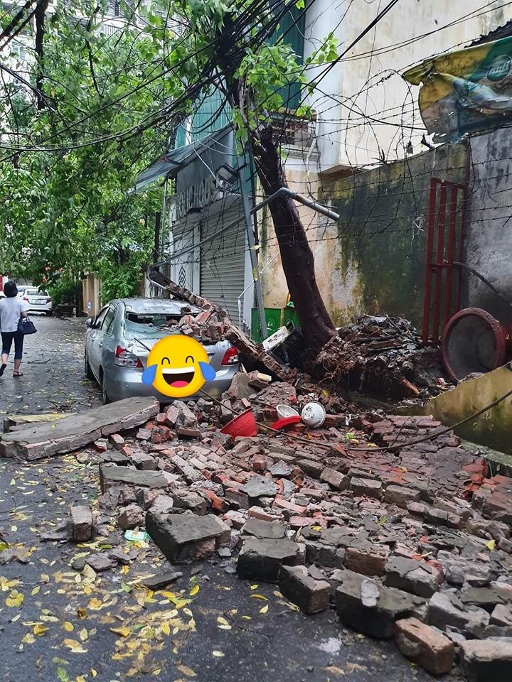 Một chiếc ô tô bị bức tường gạch đổ trúng, dẫn đến hư hỏng nặng