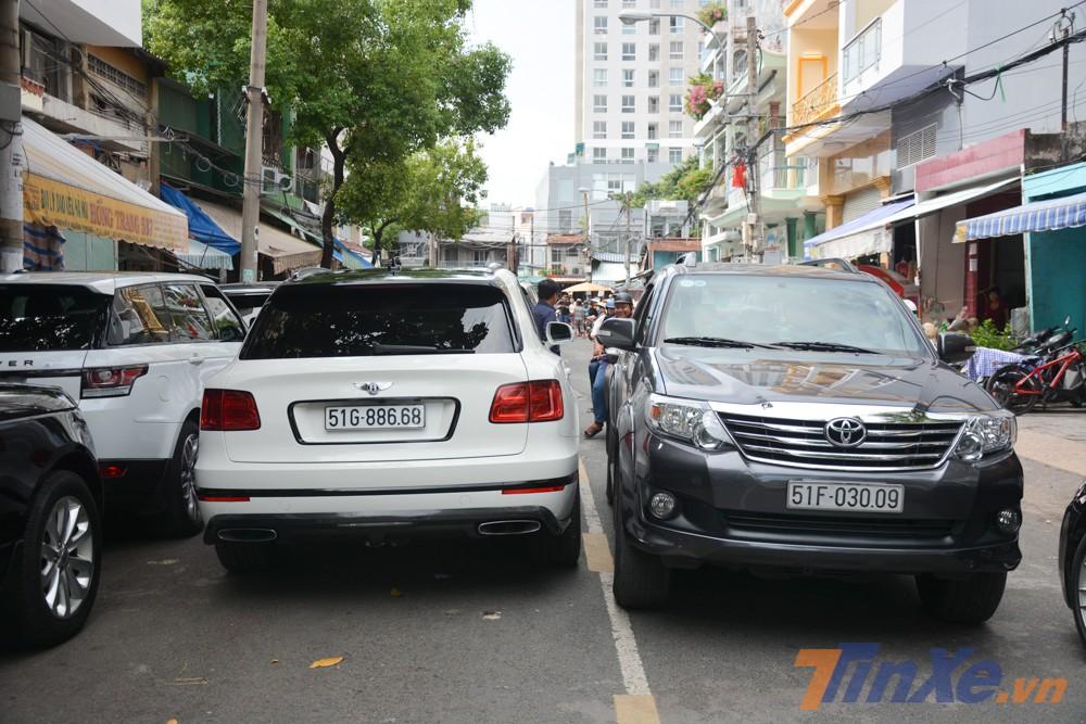 Một chiếc Toyota Fortuner lách qua khe hẹp giữa chiếc Bentley Bentayga và BMW 760 Li đỗ phía bên kia đường chừa lại