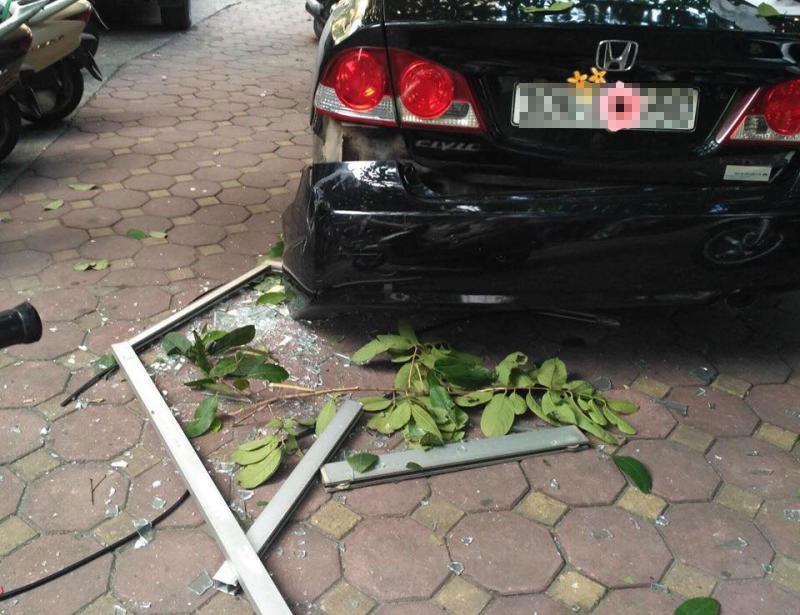 Cửa nhôm kính rơi xuống đất làm bung cản sau của chiếc Honda Civic đang đỗ
