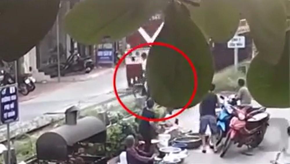 Người đàn ông dừng xe máy sát đường ray trong khi tàu hỏa đang lao tới