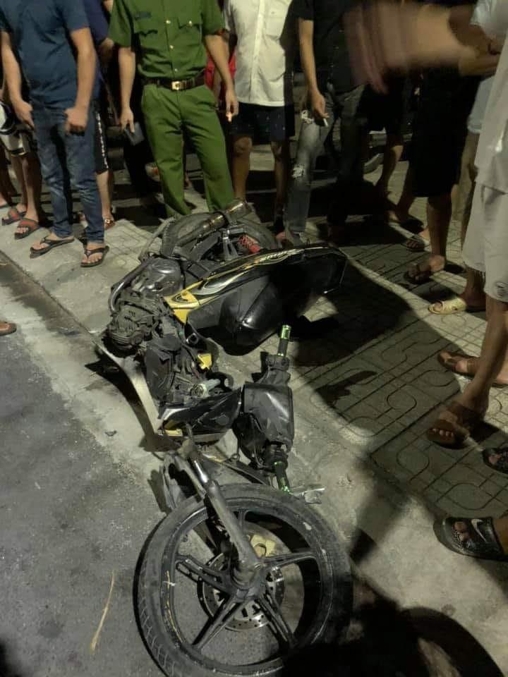 Một chiếc xe máy bị gãy đôi, nằm trên vỉa hè