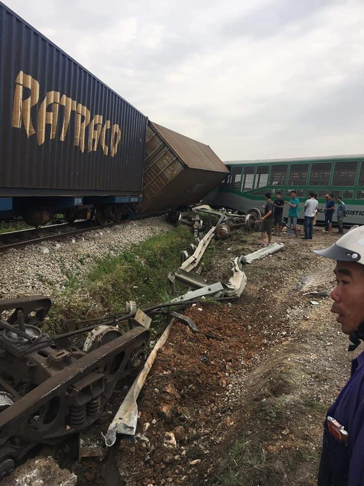 Một toa tàu nằm nghiêng trên đường ray, gác vào toa tàu khác