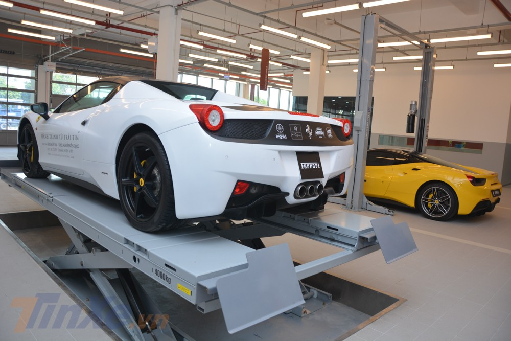 Chiếc siêu xe Ferrari 458 Spider màu trắng được cho nằm trên cầu nâng, riêng chiếc siêu xe Ferrari 488 GTB màu vàng đầu phía dưới