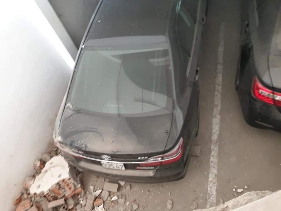 Chiếc ô tô đỗ bên dưới bị hư hỏng nhẹ đuôi xe vì mảnh vỡ của bức tường rơi trúng