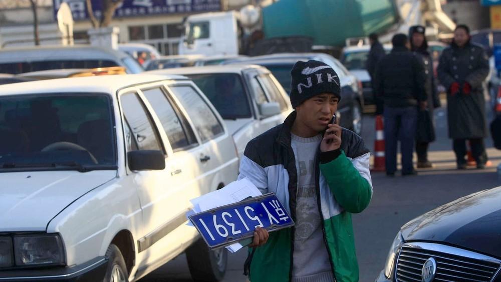 Một người đàn ông cầm trên tay biển kiểm soát ở một chợ xe cũ tại Bắc Kinh
