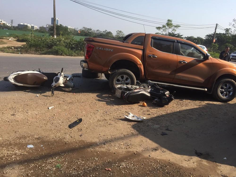 Hai chiếc xe máy nằm xung quanh chiếc xe bán tải
