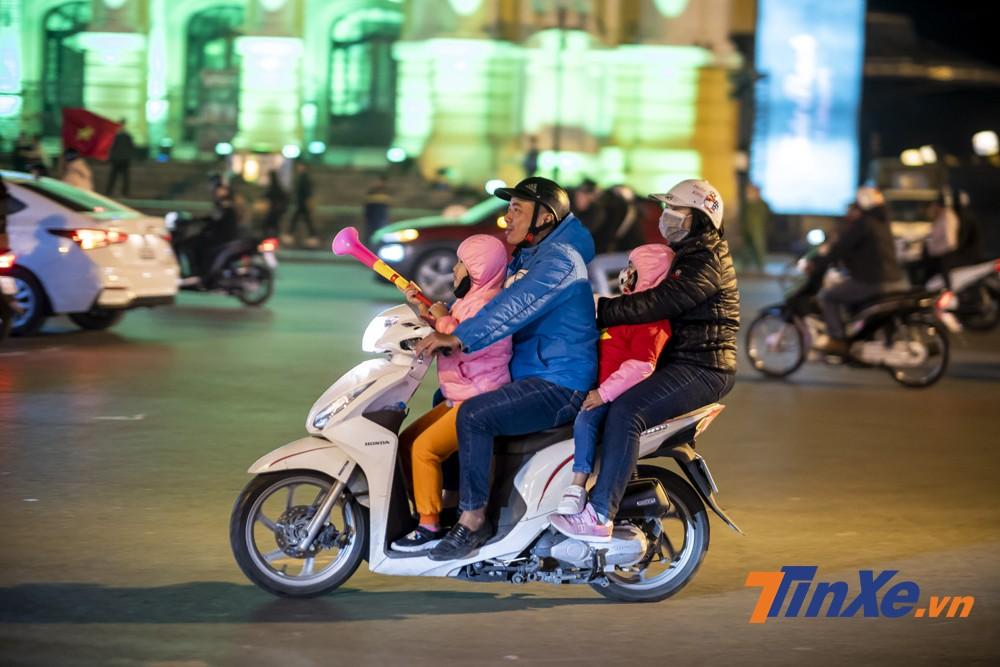 Cả gia đình trên một chiếc xe tay ga cũng xuống phố cổ vũ đội tuyển Việt Nam.a
