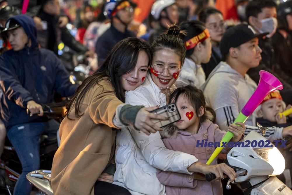 Một gia đình đi cổ vũ rất hạnh phúc nhưng quên đội mũ bảo hiểm.