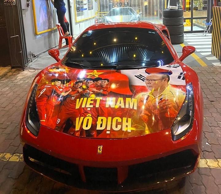Chiếc Ferrari 488 Spider được dán bộ tem có hình ảnh và cầu thủ Việt Nam. Phía bên trong là Ferrari 458 Spider của một hot girl Sài thành