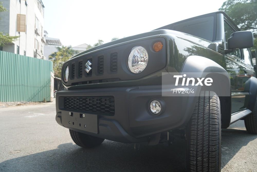 Các trang bị nổi bật có trên chiếc Suzuki Jimny thế hệ thứ 4 với giá trên 1,4 tỷ đồng trong bài viết này bao gồm ngoại thất xe sơn màu xanh rêu Solid Jungle Green kết hợp cùng các chi tiết khác được sơn đen như lưới tản nhiệt, cản va trước, các hốc gió, cản va sau, mâm xe hay lốp dự phòng. Logo chữ S phía trước đầu xe hay dòng chữ Suzuki và Jimny phía sau xe được mạ crôm sáng bóng.