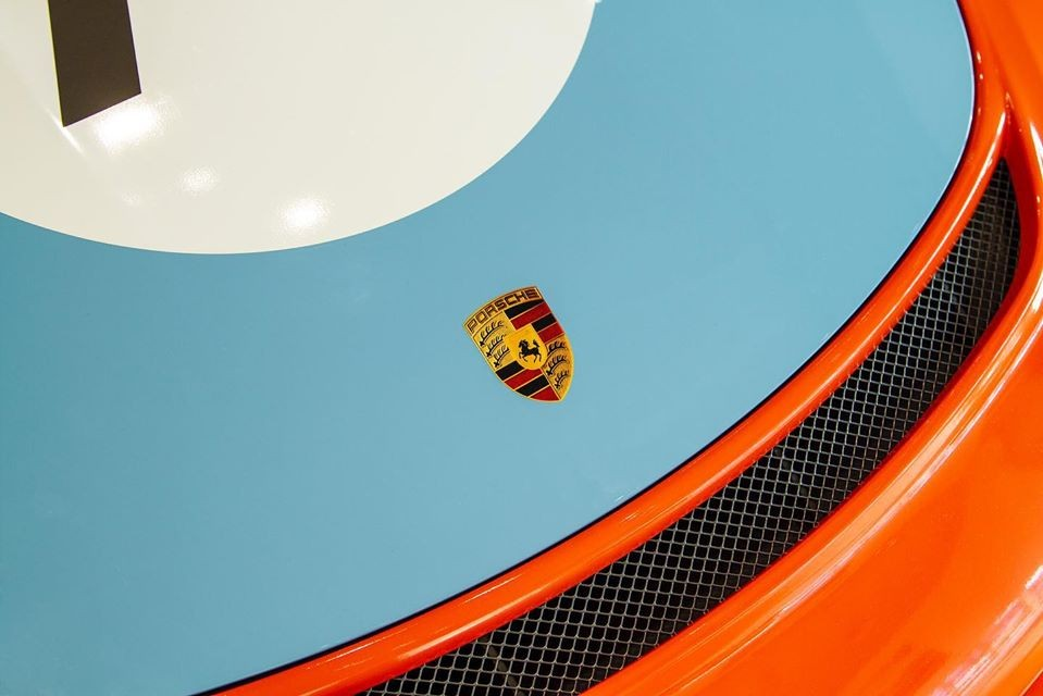 The front of this rare Porsche 911 Speedster is equipped with a striking orange color that harmonizes with the dominant blue background. Along the vehicle body is also equipped with a round logo and symbol number 70 symbolizing the 70 years of establishment and development of the Porsche brand.
