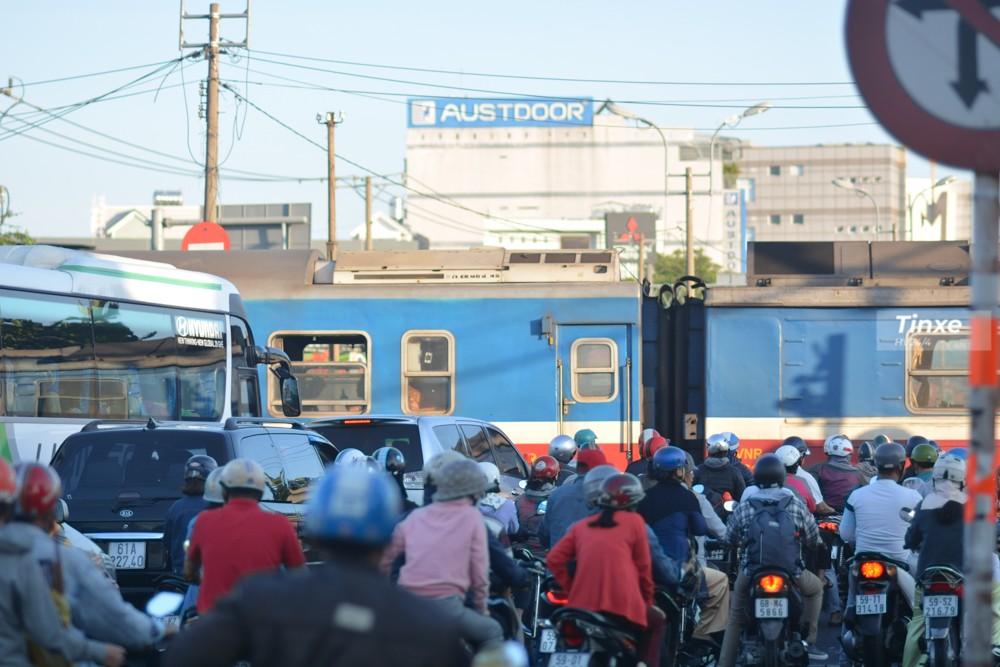 Người dân chờ đợi xe lửa đi qua tại ngã tư Bình Triệu.