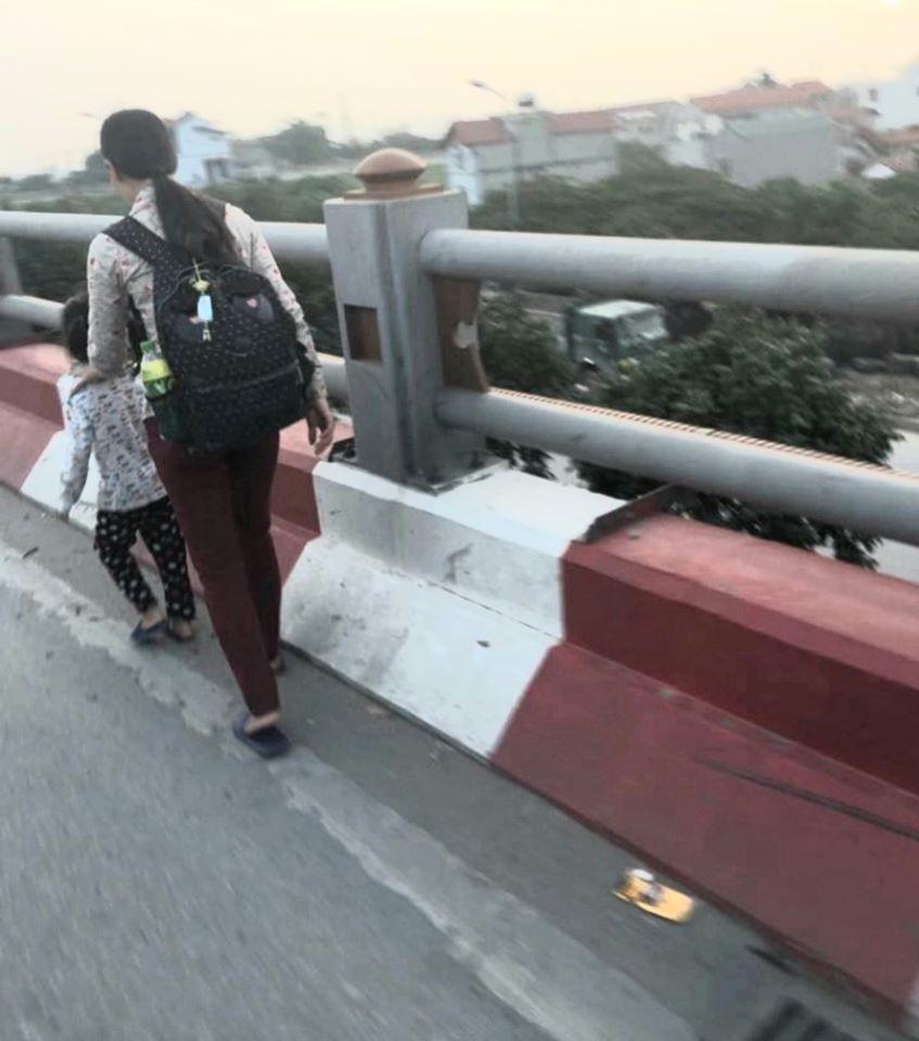 Hình ảnh hai mẹ con đi bộ ăn xin trên cầu Thanh Trì khi vụ tai nạn chưa xảy ra
