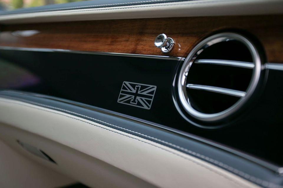 Logo hình quốc kỳ Anh với số 1 còn xuất hiện trên bảng táp-lô, trước mặt ghế phụ của xe Bentley Flying Spur First Edition 2020