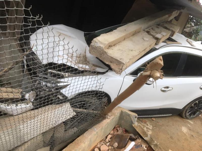 Chiếc xe Mazda CX-5 hư hỏng nặng đầu xe. Trụ bê tông mái hiên nhà dân đổ ập xuống và đè lên nóc xe ô tô