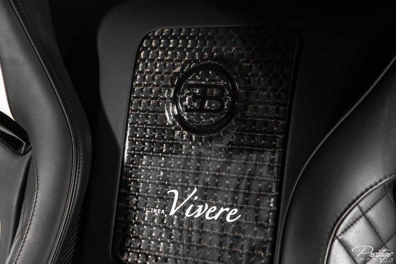 Ở giữa 2 ghế ngồi là một bảng huy hiệu carbon có logo của hãng Bugatti cùng dòng chữ Linea Vivere như dấu hiệu nhận biết đây là 1 trong 2 chiếc xe Bugatti Veyron Mansory Linea Vivere được sản xuất trên toàn thế giới.