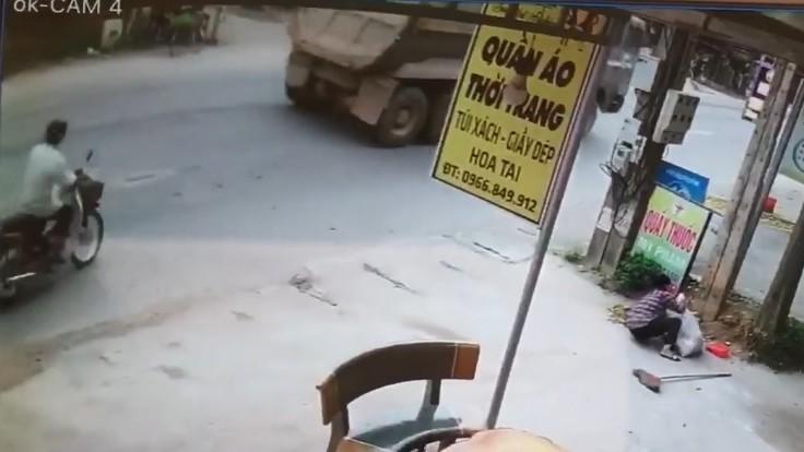 Người đàn ông điều khiển xe máy chạy ngay sau đuôi xe ben trước khi sang đường
