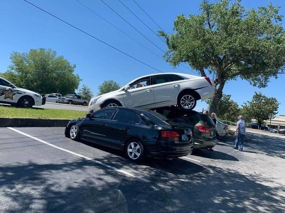 Chiếc Cadillac XTS nằm trên nóc của 2 chiếc ô tô đang đỗ