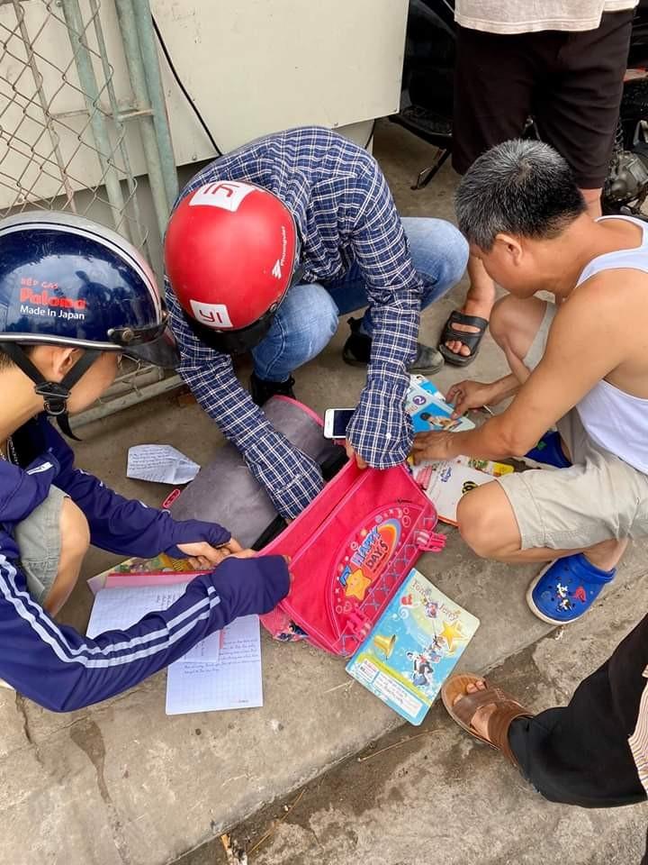 Người dân xem tập vở của em học sinh gặp nạn để thông báo người thân đến bệnh viện