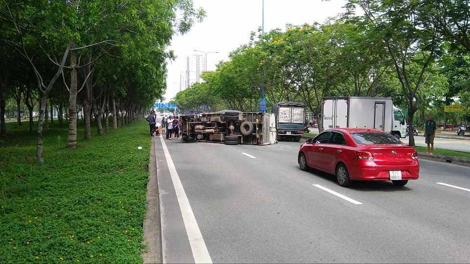 Còn đây là hình ảnh chụp lại phía sau. Có thể thấy chiếc xe tải lớn lật nghiêng nằm chắn hết 2/3 làn đường trên đại lộ Mai Chí Thọ. Làn còn lại có một chiếc xe tải nhỏ bị xe Toyota Fortuner tông trúng