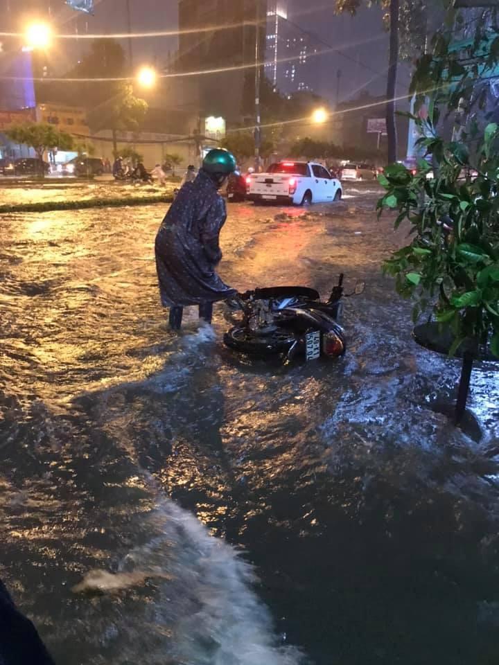 Sóng nước do những chiếc ô tô tạo ra khiến một chiếc xe máy bị đổ